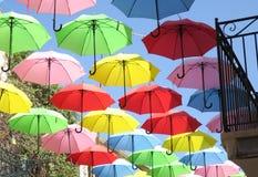 Κόκκινος, πράσινος, κίτρινος, ρόδινος, ομπρέλες που πετούν πέρα από την οδό πόλεων στοκ εικόνες