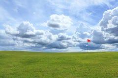 Κόκκινος πόλος στο γκολφ πράσινο Στοκ Φωτογραφίες