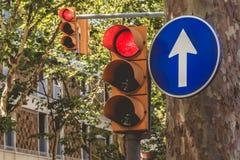 Κόκκινος σηματοφόρος δύο και ένα μπλε σημάδι της υποχρέωσης στην οδό στοκ εικόνες