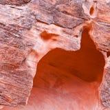 Κόκκινος τοίχος φαραγγιών βράχου με τη σπηλιά από τη διάβρωση. Στοκ Εικόνες