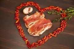 Κόκκινος - το καυτό πιπέρι είναι ευθυγραμμισμένο υπό μορφή καρδιάς Ένας κλάδος του θυμαριού, ένα γαρίφαλο του σκόρδου Σάντουιτς π Στοκ Εικόνες