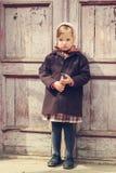 κόκκινος τρύγος ύφους κρίνων απεικόνισης Λίγο χαριτωμένο κορίτσι στο υπόβαθρο του παλαιού doo Στοκ Φωτογραφίες