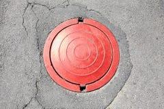 Κόκκινος υπόνομος στην άσφαλτο στοκ φωτογραφία με δικαίωμα ελεύθερης χρήσης