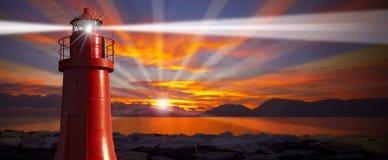 Κόκκινος φάρος με την ελαφριά ακτίνα στο ηλιοβασίλεμα Στοκ Εικόνα