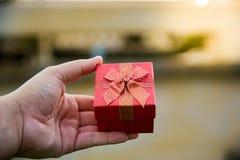 Κόκκινος-χρυσό κιβώτιο δώρων Χριστουγέννων λαβής χεριών στοκ φωτογραφία με δικαίωμα ελεύθερης χρήσης