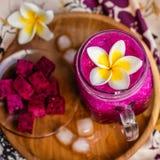 Κόκκινος χυμός φρούτων δράκων σε ένα γυαλί, που διακοσμείται με το λουλούδι Plumeria, τα φρούτα δράκων περικοπών και τους κύβους  Στοκ Εικόνα