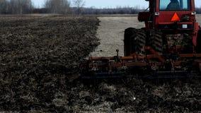 Κόκκινο αγροτικό τρακτέρ που τραβά τον καλλιεργητή που εμφανίζεται το μαύρο χώμα στον τομέα μετά από τη συγκομιδή των φασολιών σό απόθεμα βίντεο