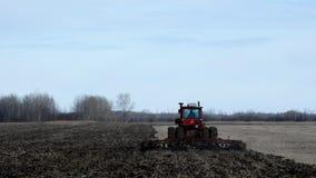 Κόκκινο αγροτικό τρακτέρ που τραβά τον καλλιεργητή που εμφανίζεται το μαύρο χώμα στον τομέα μετά από τη συγκομιδή των φασολιών σό φιλμ μικρού μήκους
