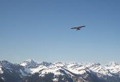 Κόκκινο αεροπλάνο που πετά πέρα από τα όρη Στοκ Φωτογραφίες