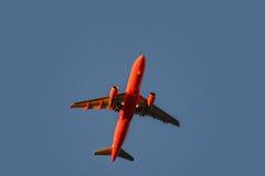 Κόκκινο αεροπλάνο στον ουρανό στο ηλιοβασίλεμα με τα φω'τα προσγείωσης επάνω Στοκ Φωτογραφία
