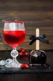 Κόκκινο αιματηρό κοκτέιλ βαμπίρ και μαύρο μήλο καραμέλας δηλητήριων Παραδοσιακή συνταγή επιδορπίων για το κόμμα αποκριών Στοκ φωτογραφία με δικαίωμα ελεύθερης χρήσης