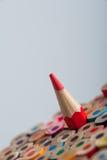 Κόκκινο ακονισμένο μολύβι μεταξύ των ζωηρόχρωμων κραγιονιών Στοκ φωτογραφία με δικαίωμα ελεύθερης χρήσης