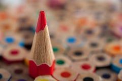 Κόκκινο ακονισμένο μολύβι μεταξύ των πολύχρωμων κραγιονιών Στοκ Εικόνες
