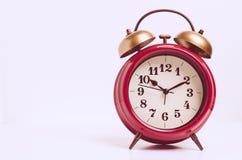 Κόκκινο αναδρομικό ρολόι ξυπνητηριού στον εκλεκτής ποιότητας τόνο Στοκ εικόνα με δικαίωμα ελεύθερης χρήσης
