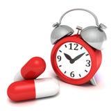 Κόκκινο αναδρομικό ρολόι συναγερμών και μεγάλα χάπια ιατρικής Στοκ εικόνα με δικαίωμα ελεύθερης χρήσης