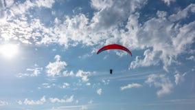 Κόκκινο ανεμοπλάνο στον μπλε νεφελώδη ουρανό Ο ήλιος στο πλαίσιο στοκ φωτογραφίες