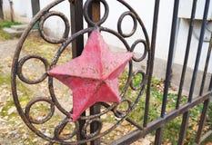 Κόκκινο αστέρι στο φράκτη σιδήρου στοκ εικόνες