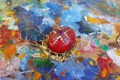 Κόκκινο αυγό Πάσχας που διακοσμείται με τον ορθόδοξο σταυρό στην παλαιά ζωηρόχρωμη καλλιτεχνική ξύλινη παλέτα στοκ φωτογραφίες με δικαίωμα ελεύθερης χρήσης