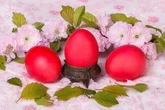 Κόκκινο αυγό τρία στο floral υπόβαθρο Στοκ Εικόνες