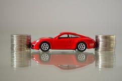 Κόκκινο αυτοκίνητο μεταξύ των νομισμάτων Στοκ Φωτογραφία