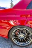 Κόκκινο αυτοκίνητο με το χρώμιο spokes και τα κόκκινα μαξιλάρια σπασιμάτων που παρουσιάζουν μεταξύ του θορίου στοκ φωτογραφίες