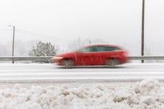 Κόκκινο αυτοκίνητο, οδήγηση βαγονιών εμπορευμάτων σταθμών γρήγορα στο δρόμο στο χειμερινό τοπίο, με το χιονώδη καιρό πηδώντας κίν στοκ φωτογραφία με δικαίωμα ελεύθερης χρήσης