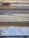 Κόκκινο αυτοκίνητο στο οδικό ελαφρύ χιονισμένο έδαφος στοκ φωτογραφία με δικαίωμα ελεύθερης χρήσης