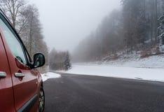 Κόκκινο αυτοκίνητο στο χειμερινό δρόμο στα βουνά, δάσος με το χιόνι στοκ φωτογραφία με δικαίωμα ελεύθερης χρήσης
