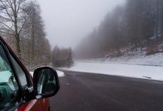 Κόκκινο αυτοκίνητο στο χειμερινό δρόμο στα βουνά, δάσος με το χιόνι στοκ εικόνα