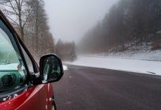 Κόκκινο αυτοκίνητο στο χειμερινό δρόμο στα βουνά, δάσος με το χιόνι στοκ φωτογραφία