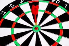 Κόκκινο βέλος βελών που χτυπά στο κέντρο στόχων του dartboard Στοκ Φωτογραφία