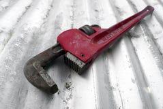 Κόκκινο γαλλικό κλειδί σωλήνων στο ζαρωμένο υπόβαθρο σιδήρου Στοκ φωτογραφίες με δικαίωμα ελεύθερης χρήσης