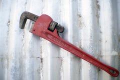 Κόκκινο γαλλικό κλειδί σωλήνων στο ζαρωμένο υπόβαθρο σιδήρου Στοκ εικόνες με δικαίωμα ελεύθερης χρήσης