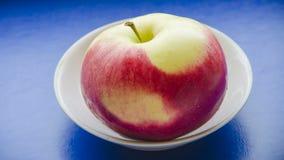 Κόκκινο διαμορφωμένο μήλο σε ένα μπλε υπόβαθρο Στοκ Φωτογραφία