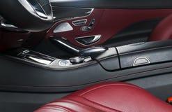 Κόκκινο διατρυπημένο εσωτερικό δέρματος του σύγχρονου αυτοκινήτου πολυτέλειας Άνετα κόκκινα καθίσματα και πολυμέσα δέρματος Τιμόν Στοκ Εικόνες
