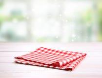 Κόκκινο διπλωμένο gingham ύφασμα πικ-νίκ στον πίνακα στοκ φωτογραφία με δικαίωμα ελεύθερης χρήσης