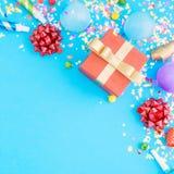 Κόκκινο δώρων κομφετί κομμάτων κιβωτίων διάφορο, μπαλόνια, στο μπλε backgroun Στοκ Φωτογραφίες