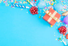 Κόκκινο δώρων κομφετί κομμάτων κιβωτίων διάφορο, μπαλόνια, στο μπλε backgroun Στοκ εικόνα με δικαίωμα ελεύθερης χρήσης