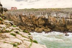 Κόκκινο εγκαταλειμμένο σπίτι που βρίσκεται στην κορυφή ενός φυσικού απότομου βράχου στοκ εικόνες