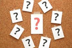 Κόκκινο ερωτηματικό σε ένα κομμάτι χαρτί και πολλά ερωτηματικά στον πίνακα φελλού στοκ εικόνες