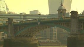 Κόκκινο λεωφορείο που δίνει τη γέφυρα Southwark, πόλη του Λονδίνου στο υπόβαθρο απόθεμα βίντεο