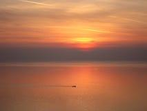 Κόκκινο ηλιοβασίλεμα πέρα από τον ωκεανό και λίγη βάρκα Στοκ εικόνες με δικαίωμα ελεύθερης χρήσης