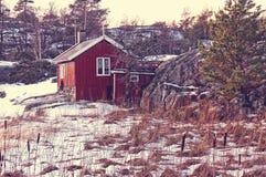 Κόκκινο θερινό εξοχικό σπίτι μεταξύ των βράχων Στοκ Εικόνες