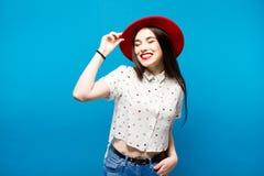 Κόκκινο θηλυκό καπέλο πιλήματος Απομονωμένος στην μπλε ανασκόπηση Ευτυχής και φρέσκος Στοκ Φωτογραφία