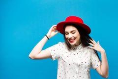 Κόκκινο θηλυκό καπέλο πιλήματος Απομονωμένος στην μπλε ανασκόπηση Ευτυχής και φρέσκος Στοκ Φωτογραφίες