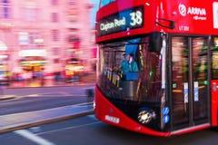 Κόκκινο διπλό λεωφορείο καταστρωμάτων στη θαμπάδα κινήσεων στην κυκλοφορία νύχτας του Λονδίνου Στοκ Εικόνα