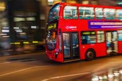 Κόκκινο διπλό λεωφορείο καταστρωμάτων στη θαμπάδα κινήσεων στην κυκλοφορία νύχτας του Λονδίνου Στοκ Φωτογραφίες