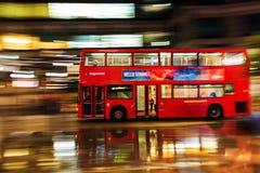 Κόκκινο διπλό λεωφορείο καταστρωμάτων στη θαμπάδα κινήσεων στην κυκλοφορία νύχτας του Λονδίνου Στοκ Εικόνες
