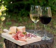 Κόκκινο και άσπρο κρασί σε ένα γυαλί με το λουκάνικο και το ζαμπόν Στοκ Φωτογραφία
