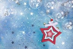 Κόκκινο και άσπρο ξύλινο αστέρι με τις σφαίρες Χριστουγέννων γυαλιού στην μπλε ΤΣΕ Στοκ Φωτογραφίες